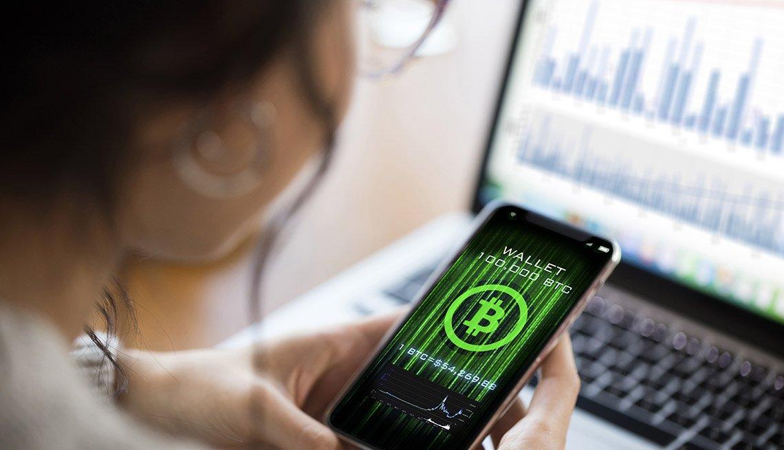 Mujer mirando un símbolo de bitcóin en la pantalla de su teléfono y con una computadora alfondo.