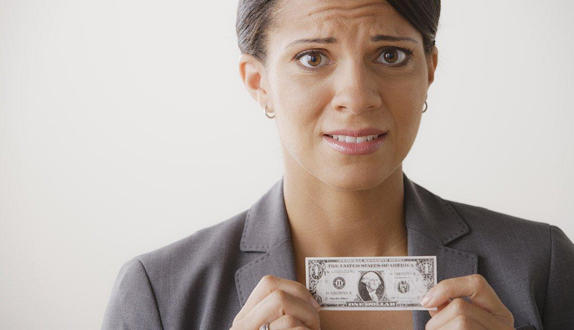 Mujer con cara de angustia y sosteniendo mini billete de un dólar