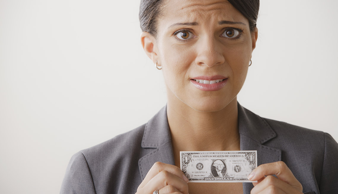 worried expression on a woman's face as she holds a shrinking dollar in front of her