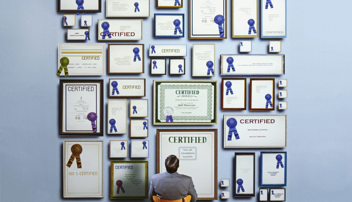 view from behind a man looking up at a wall filled with framed certificates with impressive blue ribbons that look fake