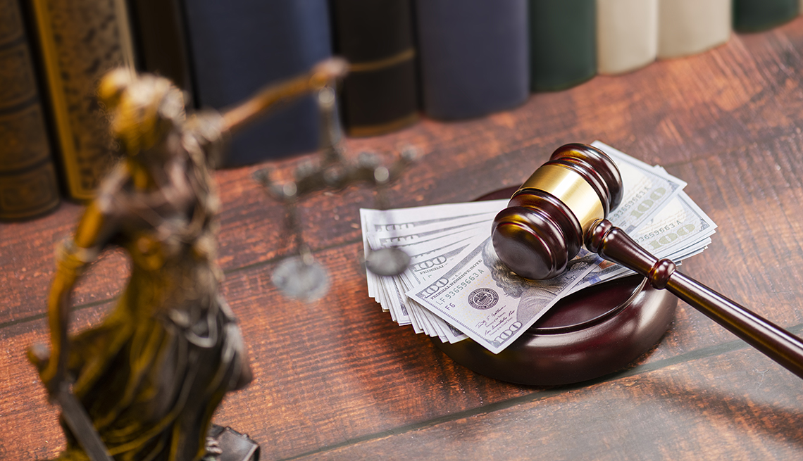 Varios dólares debajo de un mazo de juzgado sobre un escritorio