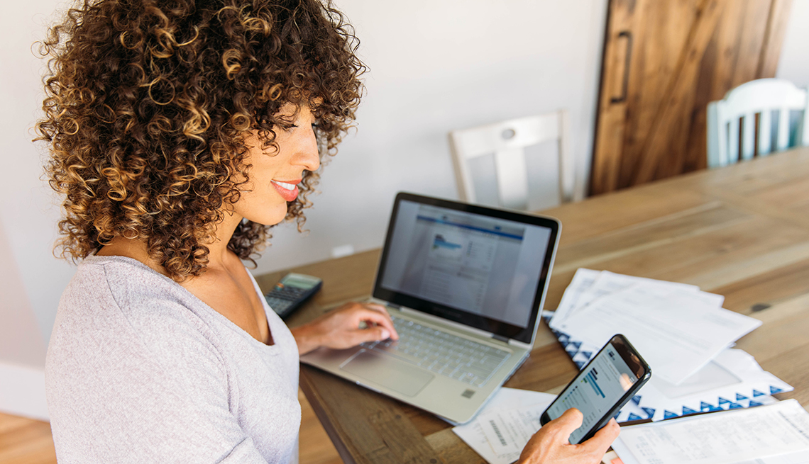 A woman seated at the dining table looks confident managing her finances with her smartphone, laptop and print out account statements