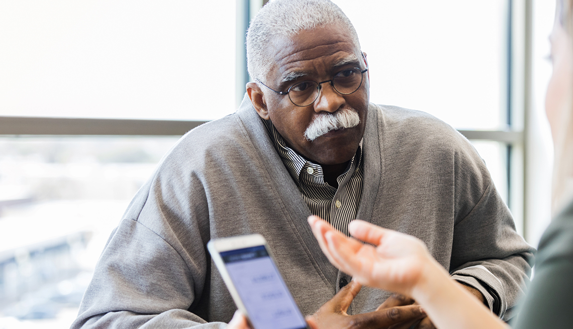 Persona mayor recibiendo información acerca de un préstamo en una cooperativa