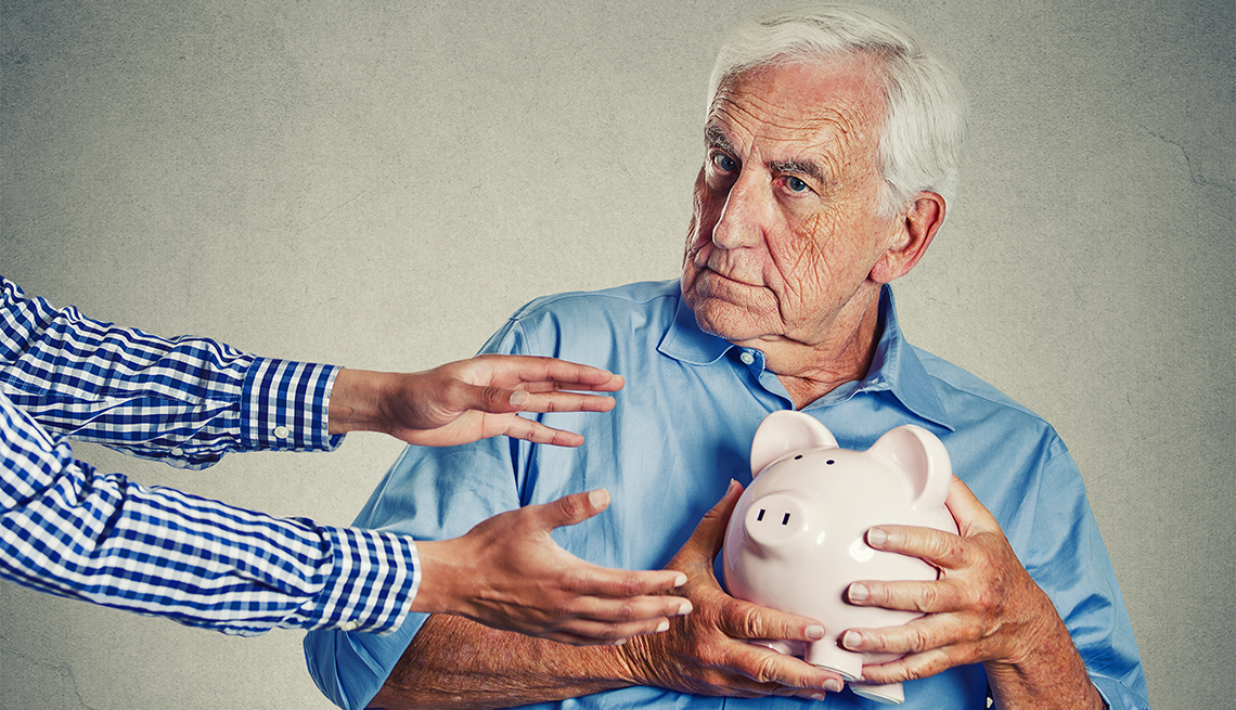 man holding protecting piggy bank from searching hands