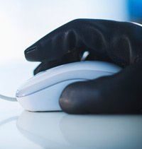 A gloved hand on a computer mouse