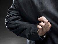 Corredor de la bolsa con los dedos cruzados - Nuevas estafas a los inversionistas