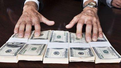 Manos de un hombre sobre billetes de 100 dólares
