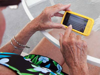 Senior woman using smartphone - twitter scams take you to forms trying to glean personal information.