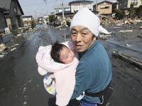 Al oír otra alerta de tsunami, un padre intenta ponerse a salvo con su bebé de cuatro meses de edad que fue rescatada de los escombros del terremoto ocurrido en Japón el 11 de marzo del  2011