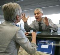 Hombre discutiendo con un asistente en un terminal aéreo