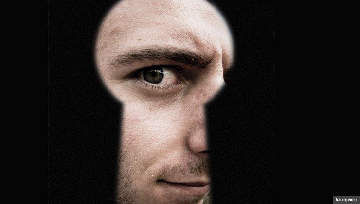 A man peers through a keyhole representing door-to-door sales scams.