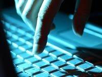 Una mano tocando un teclado en un cuarto oscuro - Consejos sobre cómo crear un código PIN memorable que no sea fácil de adivinar por los delincuentes.