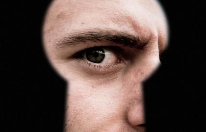 Hombre mirando a través de un ojo de cerradura que representa de puerta a puerta estafa ventas, Alerta de estafa
