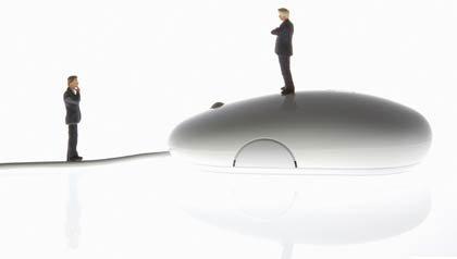 Dos hombres con un ratón de computador - Los correos electrónicos de los estafadores pueden ser disfrazados fácilmente para parecer que son de un amigo.