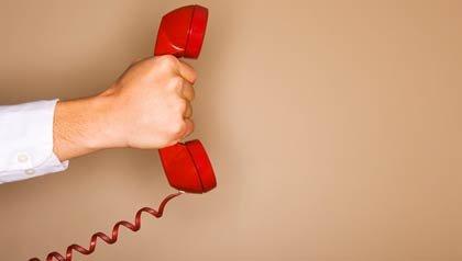 Hombre sosteniendo un teléfono rojo de alerta - prevenga las estafas por teléfono