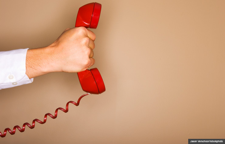Man holding red phone, Scam alert for robocalls posing as cardholder services