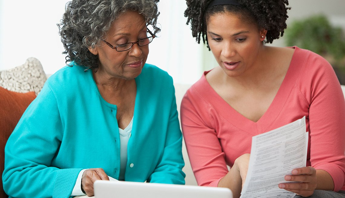 Mother and daughter looking at paperwork. Protect your parents from scams.