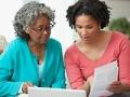 Madre e hija revisando papeles. Proteja a sus padres de las estafas.