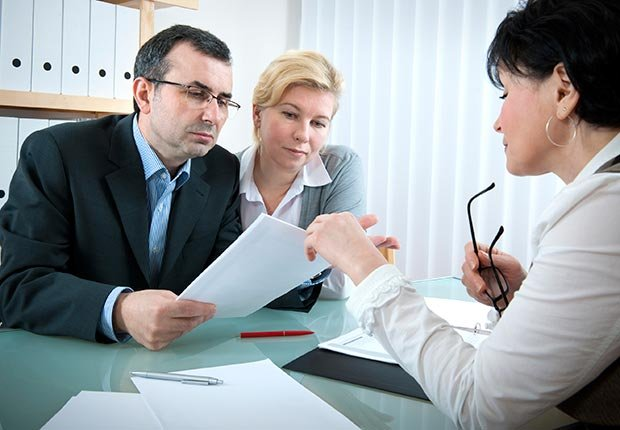 A tax preparer helps a couple, Avoid tax-break scams (iStock)