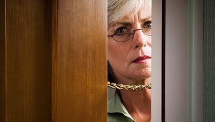 Mujer mirando por la puerta de su casa - Alerta de estafas