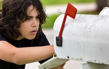 A young man stealing the mail from a mailbox, Scam Alert: Early season tax filing scams