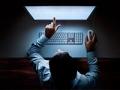 Un hombre trabaja con su computador en la oscuridad, Tenga cuidado con los fraudes