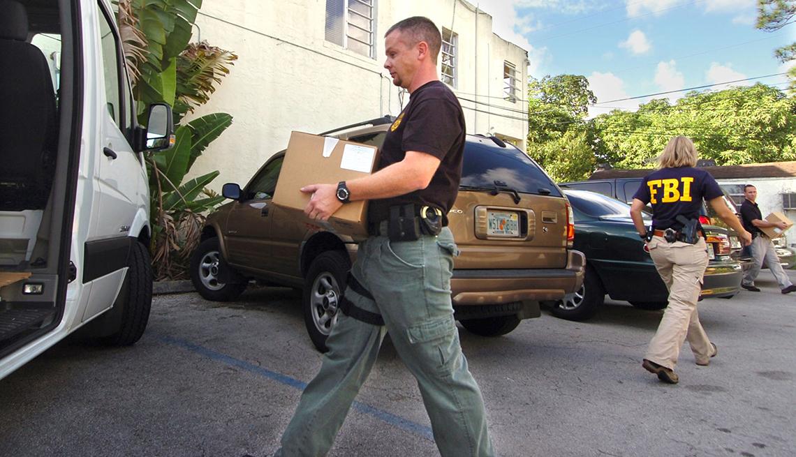 Agentes del FBI colocando cajas con documentos en una camioneta como evidencia de fraude en el Medicare en Miami.