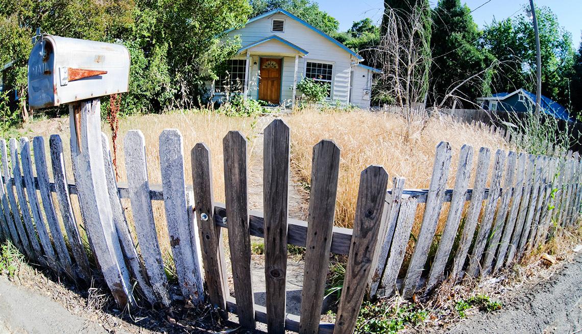 Casa con apariencia de abandono rodeada por una reja de madera