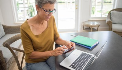 Woman using cell phone and laptop in living room