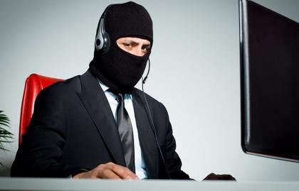 Hombre vestido con corbata, con un pasamontañas y un sistema de manos libres para computador - Estafas de asistencia técnica