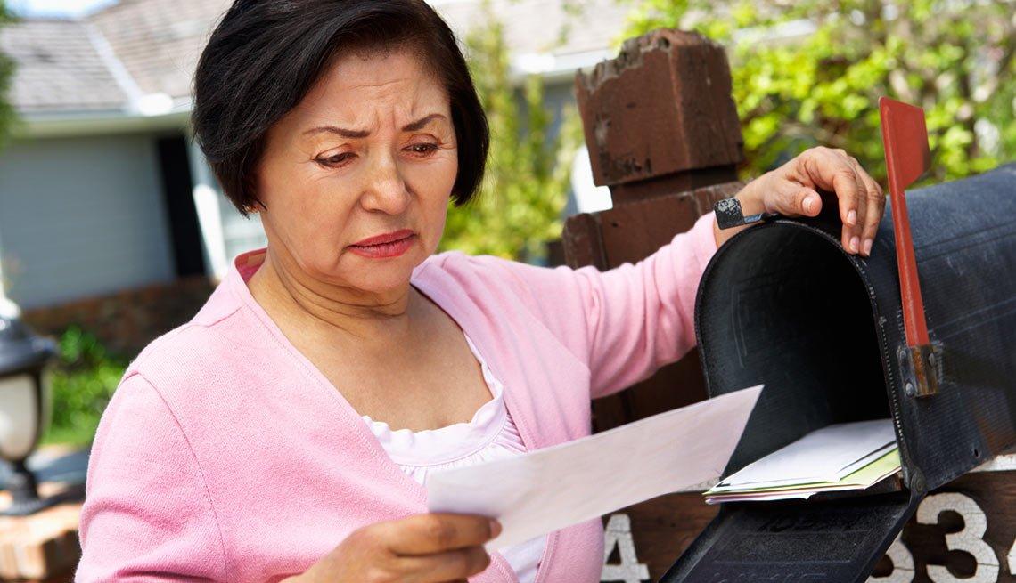 Mujer mayor chequeando el buzon de correo - Estafa impostor del IRS