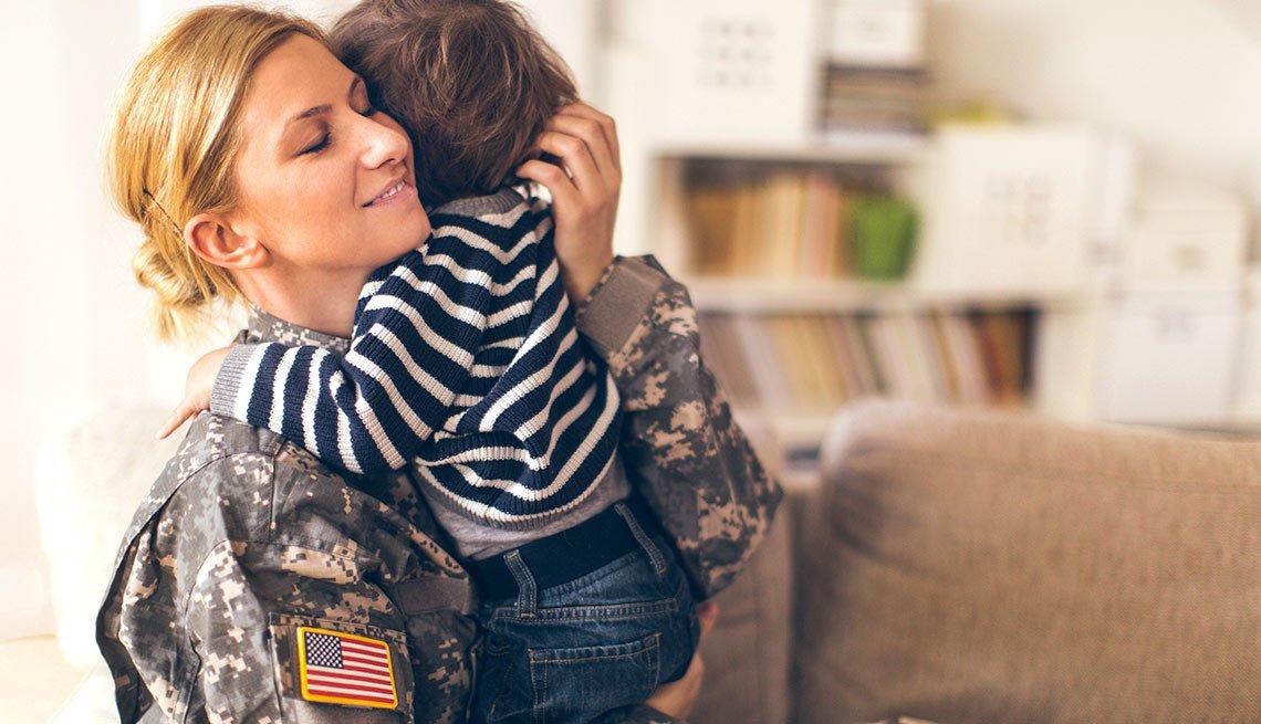 Mujer soldado abrazando a un niñito