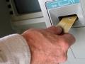 Hombre usando su tarjeta de crédito en una ATM
