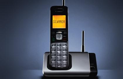 Teléfono inhalámbrico fijo con la palabra scammer 'estafador' en la pantalla - Cuidado con las nuevas estafas