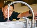 Hombre revisando la plomería de una cocina - Estafas en reparaciones domésticas