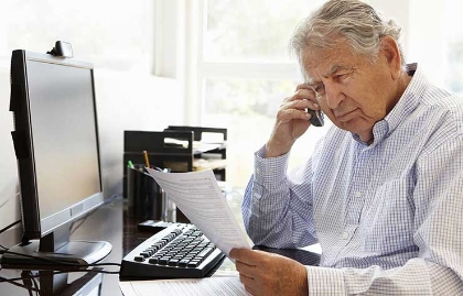 Hombre mayor sentado frente a una computadora sosteniendo un teléfono y unos papeles - Bancos reciben recomendaciones para proteger a personas mayores