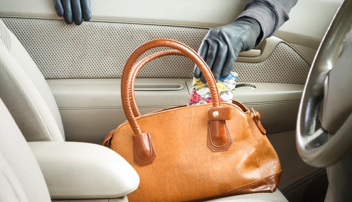 Formas de protegerte contra el robo de identidad - manos con un guantes negros sacando una billetera de un bolso dejado en el interior de un carro