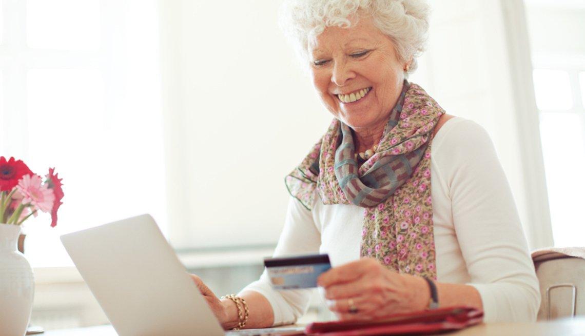 Formas de protegerte contra el robo de identidad - Mujer mayor viendo una tarjeta de crédito y viendo la pantalla de su computadora personal