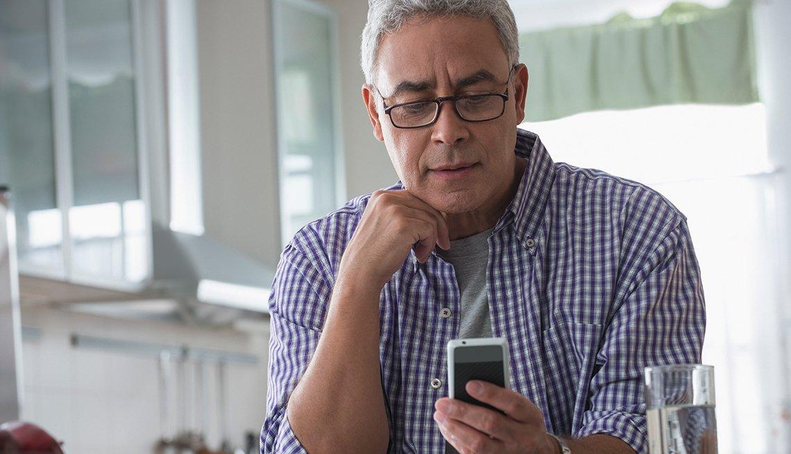 Hombre usando un teléfono móvil en una cocina y cuidado con las cosas que no debes publicar en internet