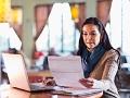 Mujer en un café revisando cuentas en un computador, pero si usas una red wifi pública hay cosas que no deberías hacer