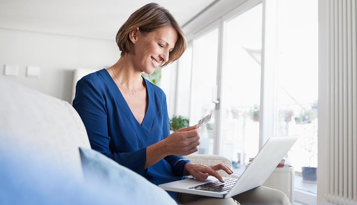 Mujer viendo facturas y con una computadora portátil sobre las piernas