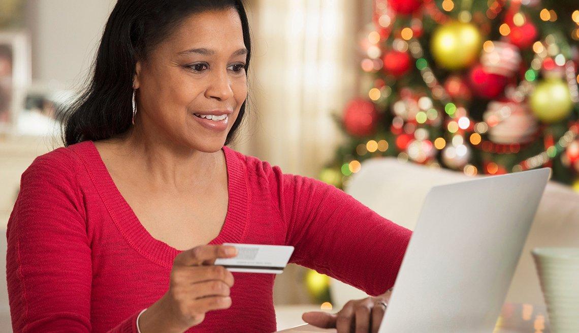 Mujer comprando en línea desde la casa en la temporada de fiestas