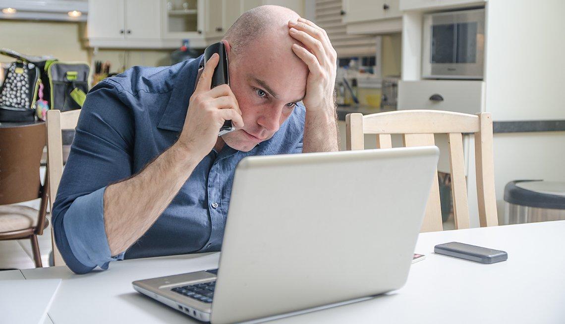 Hombre mirando su computadora mientras escucha por un teléfono