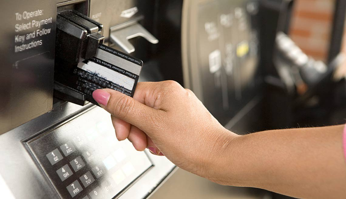 Mano de una mujer colocando una tarjeta de débito en una máquina pública.