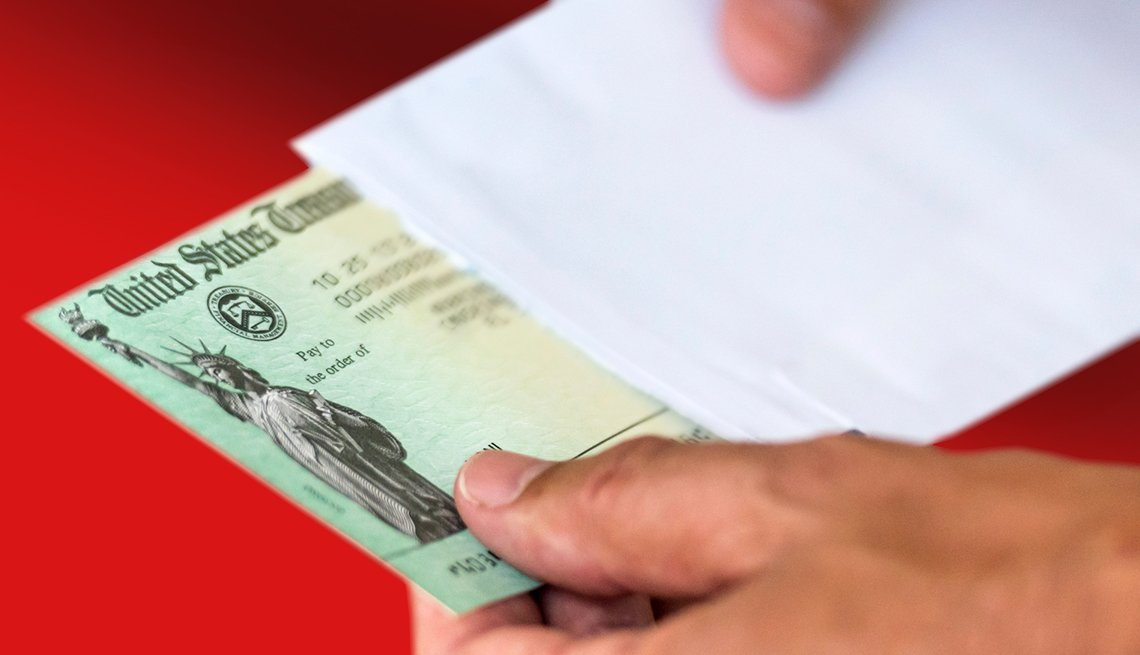Person sliding a Social Security check out of a white envelope