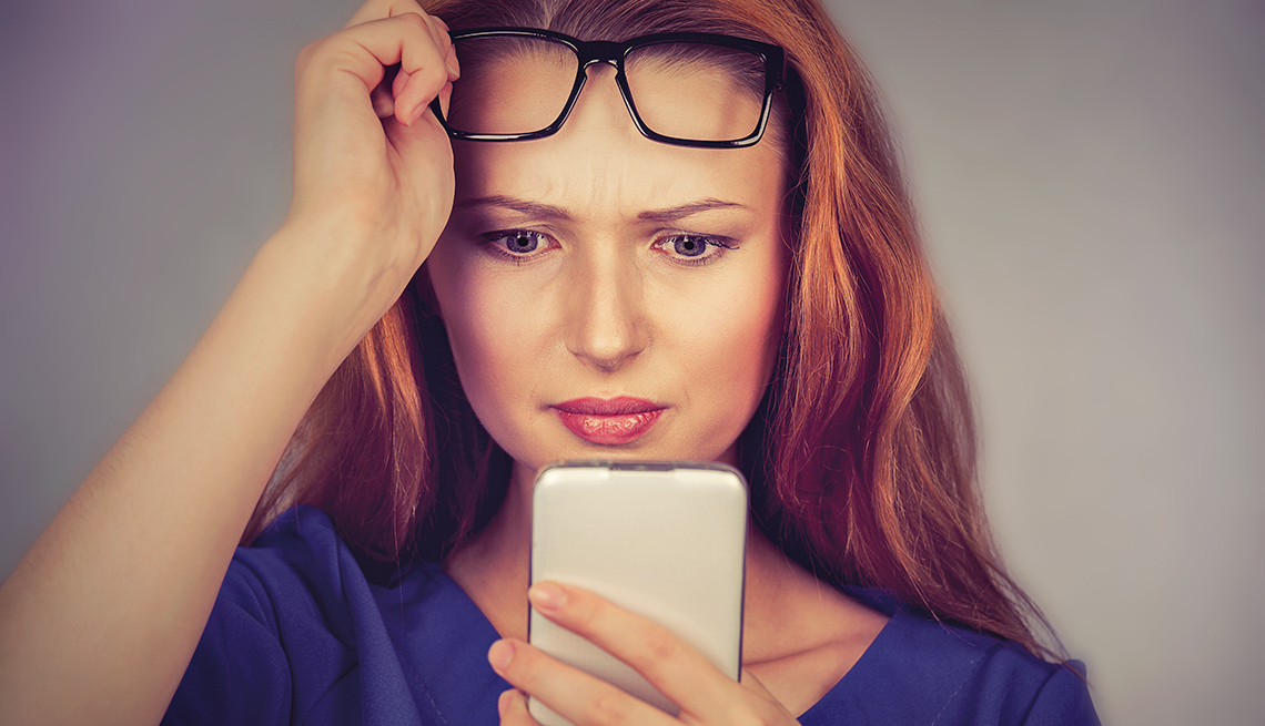 woman looks surprised while looking at phone