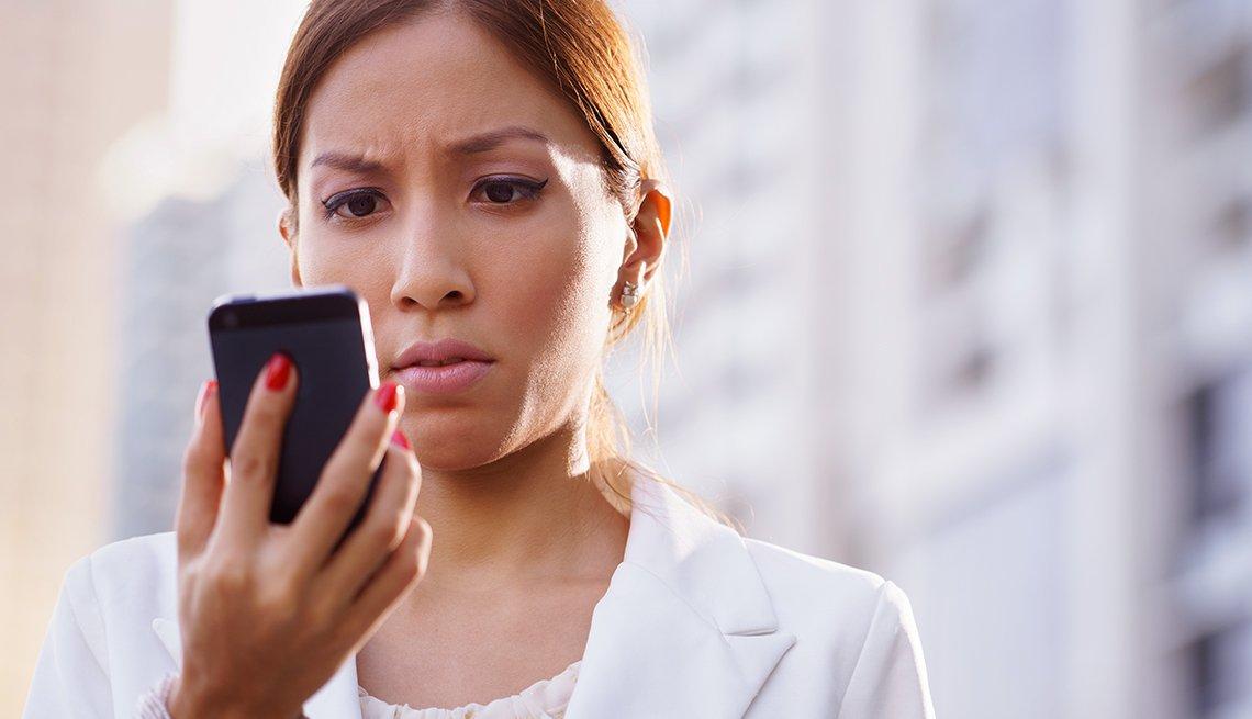 Mujer mirando a un teléfono móvil