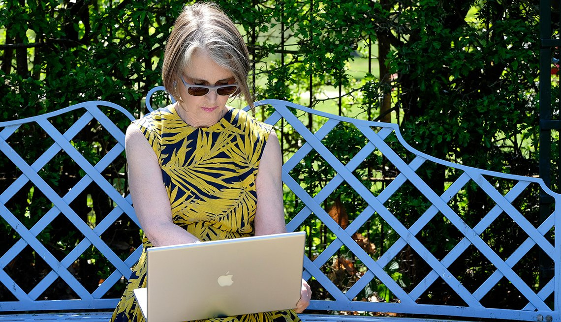 Woman wearing sunglasses using her computer outside