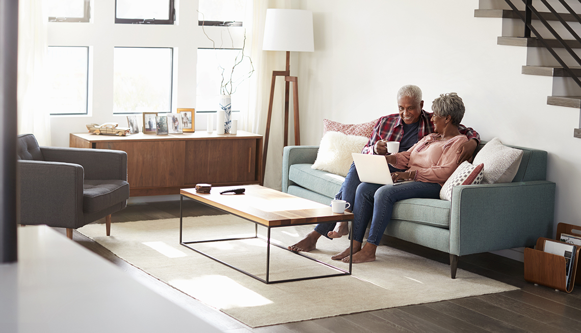 item 1 of Gallery image - Couple Sitting On Sofa At Home Using Laptop