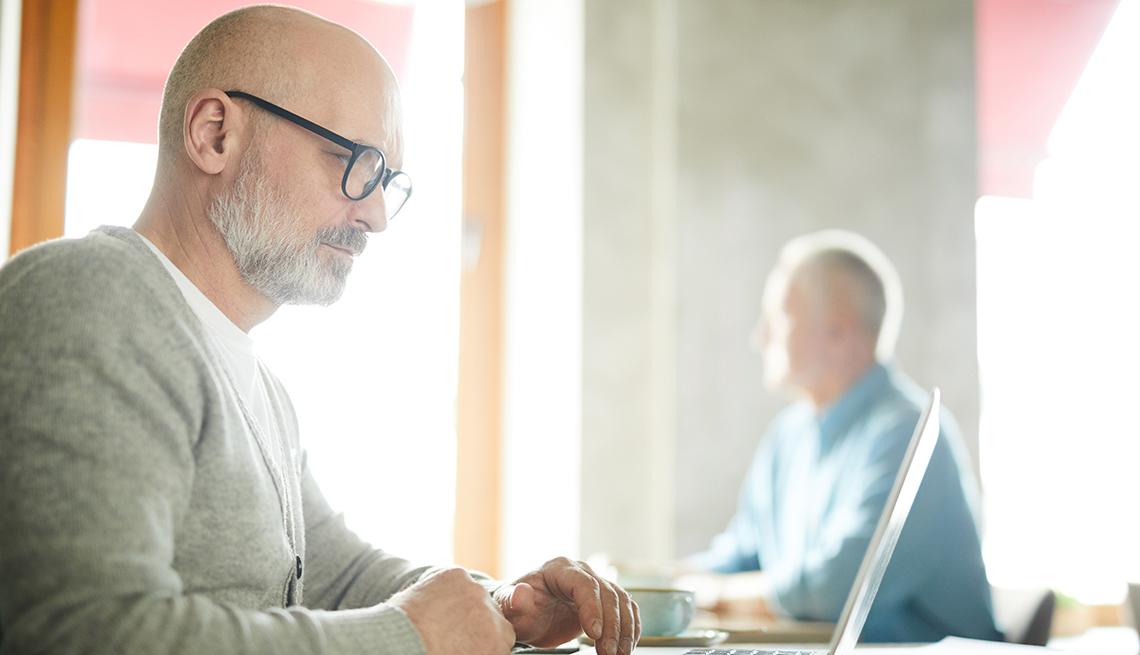 item 9 of Gallery image - Hombre viendo su computadora portátil en un café